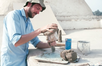 Experimenting with materials: In the 1980s, especially, Amarna became something of a hub of experimental archaeology (www.amarnaproject.com/pages/publications/tech.shtml). Here Paul Nicholson shapes a hemispherical clay mould for making bread over a wooden form or patrix; cylindrical bread moulds can be seen drying in the background.